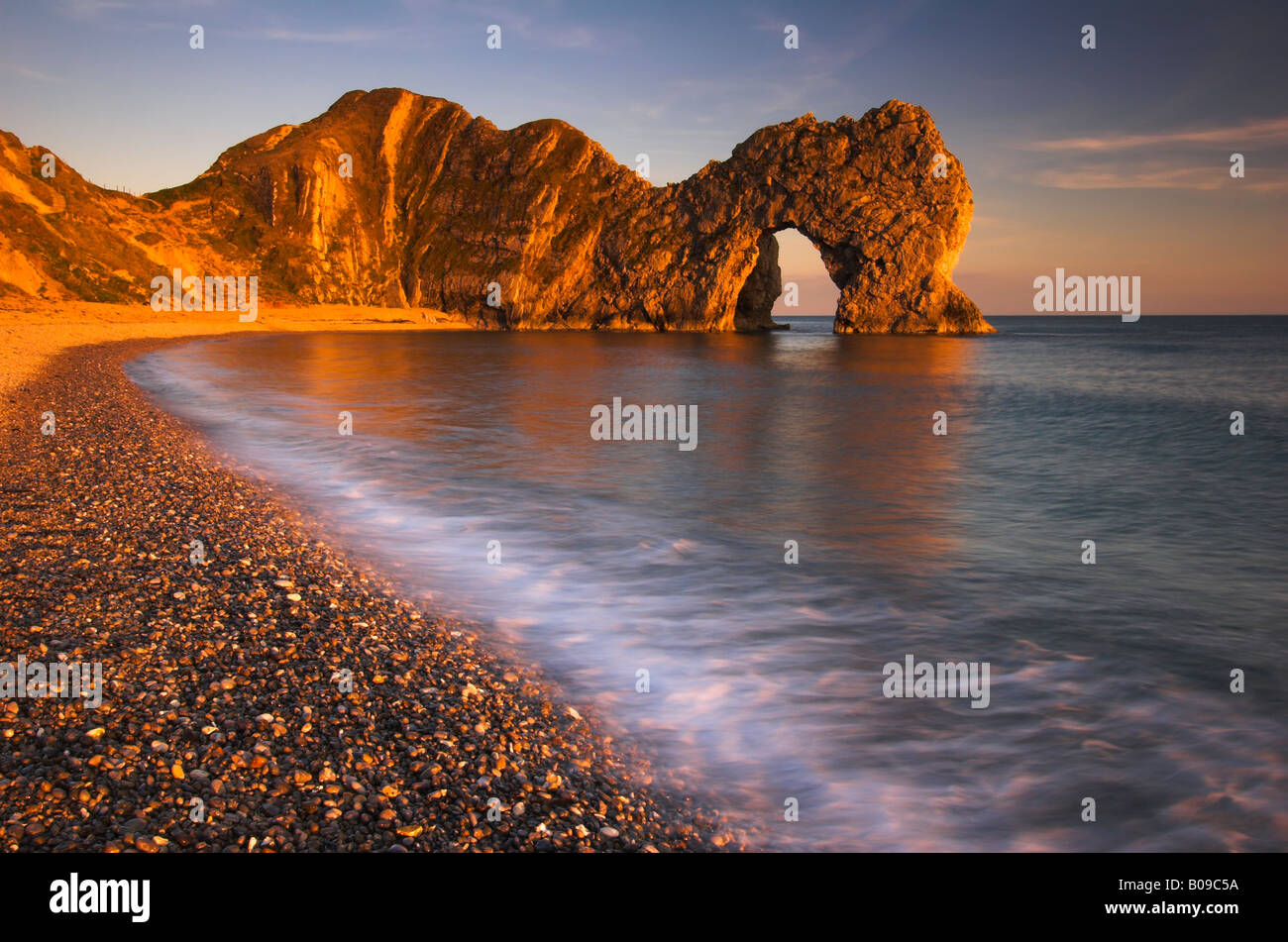 Golden sunlight catches the natural rock arch at Durdle Door in Dorset - Stock Image
