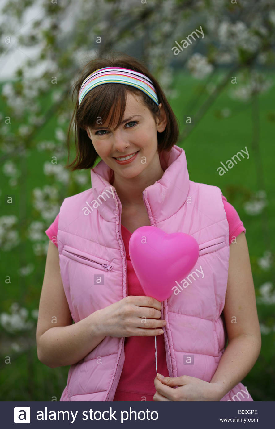 woman with pink heart-shaped balloon - Stock Image