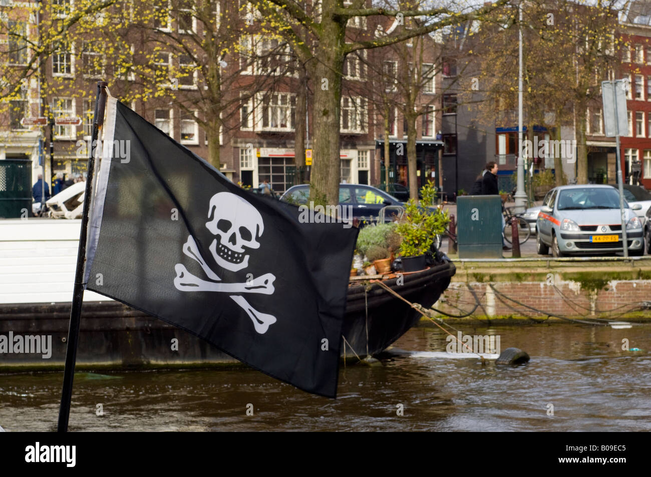 Amsterdam, Skull and Crossbones or jolly roger pirate flag on a houseboat on Prinsengracht canal - Stock Image