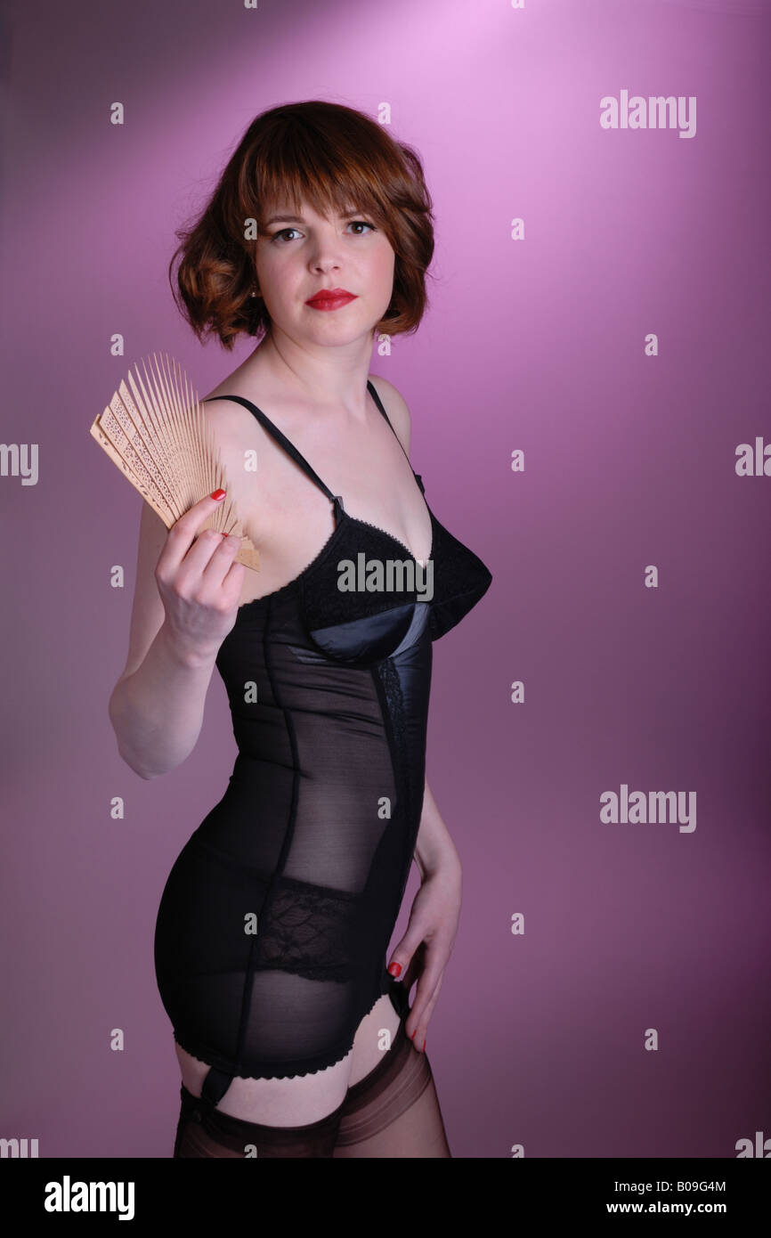 d89c8ebe581 attractive retro fifties pinup girl in vintage lingerie and nylon stockings  with hand fan