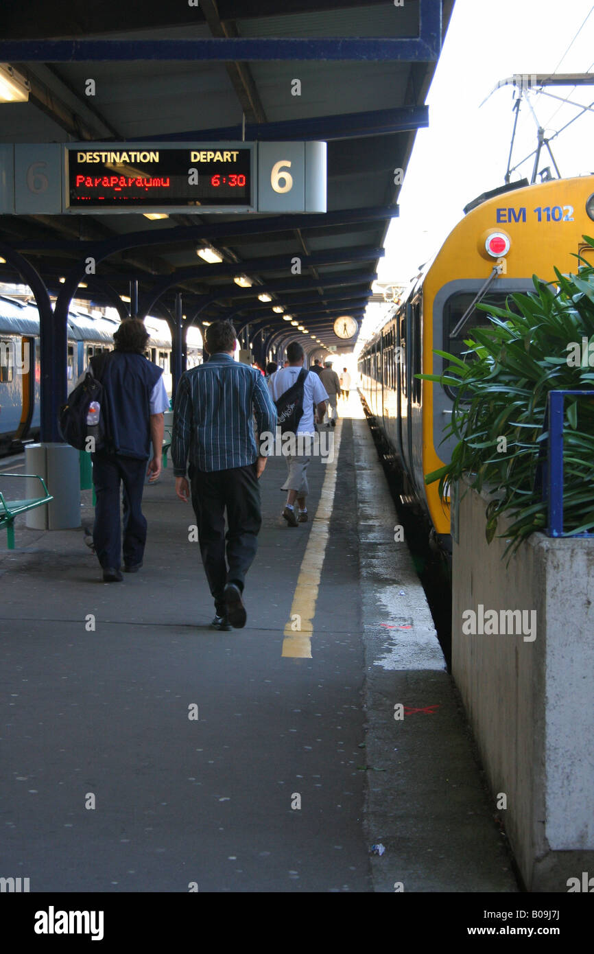 Commuters at railway station walking down the platform to the train. - Stock Image
