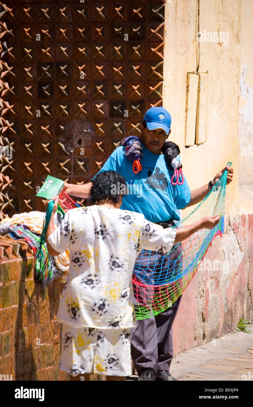 Man selling hammocks to a woman outside a church in mexico - Stock Image