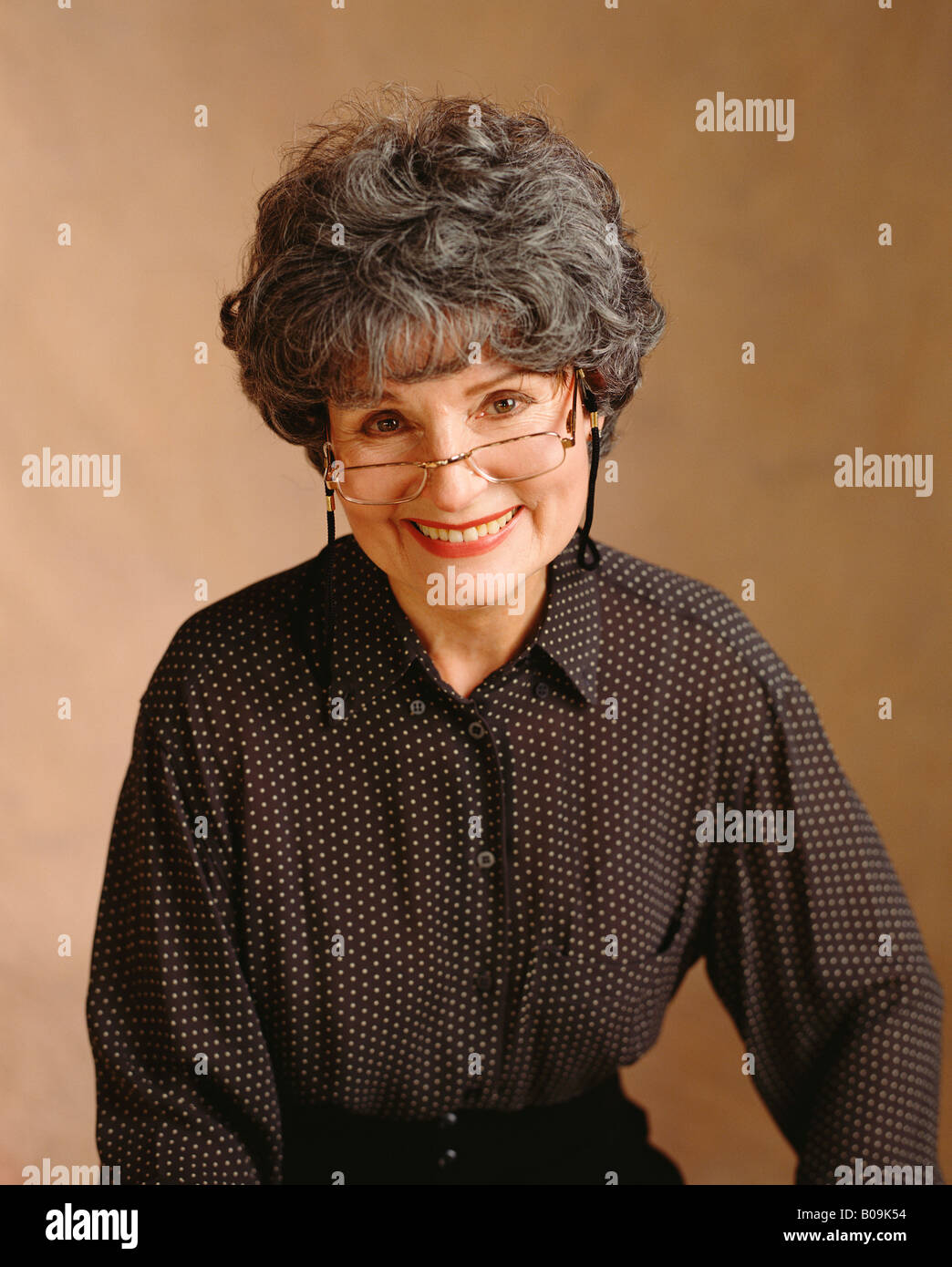 ab900b4a73 An happy smile from an older woman with gray hair and reading glasses in a studio  portrait