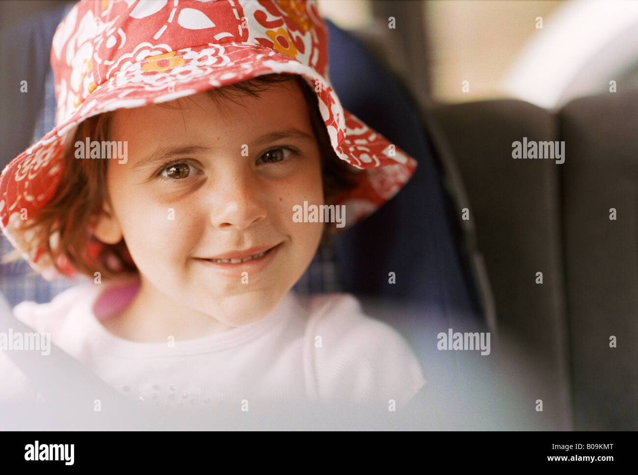 dad8cf7c0a9 A little girl smiling with a cute red floppy hat in a child safe car seat