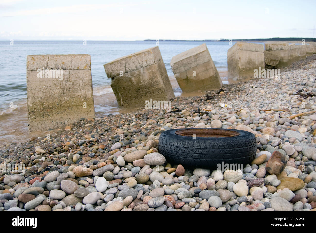 A tyre and concrete obstacles on Roseisle Beach - Stock Image
