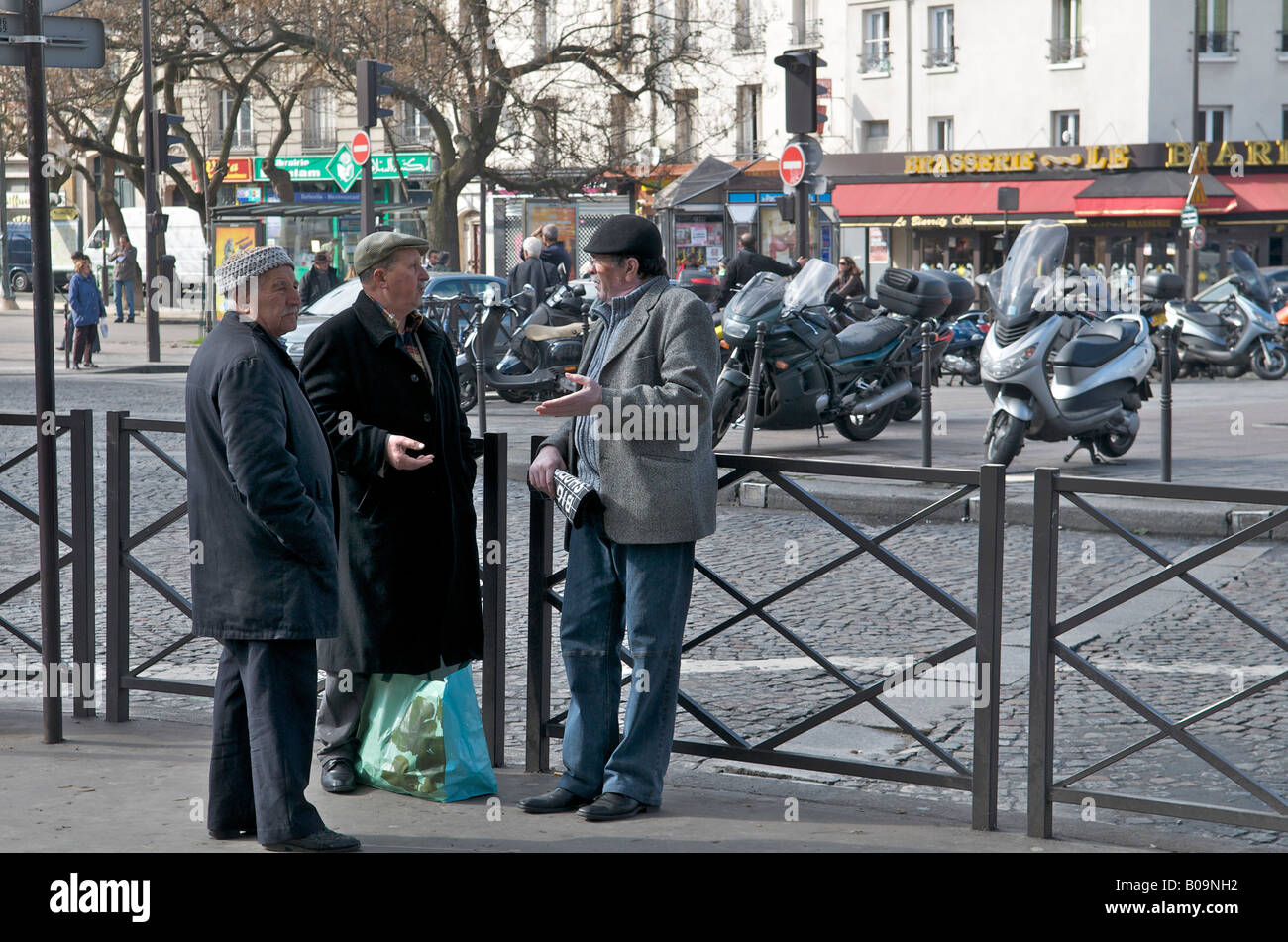 Frenchmen talking on the street in Paris - Stock Image