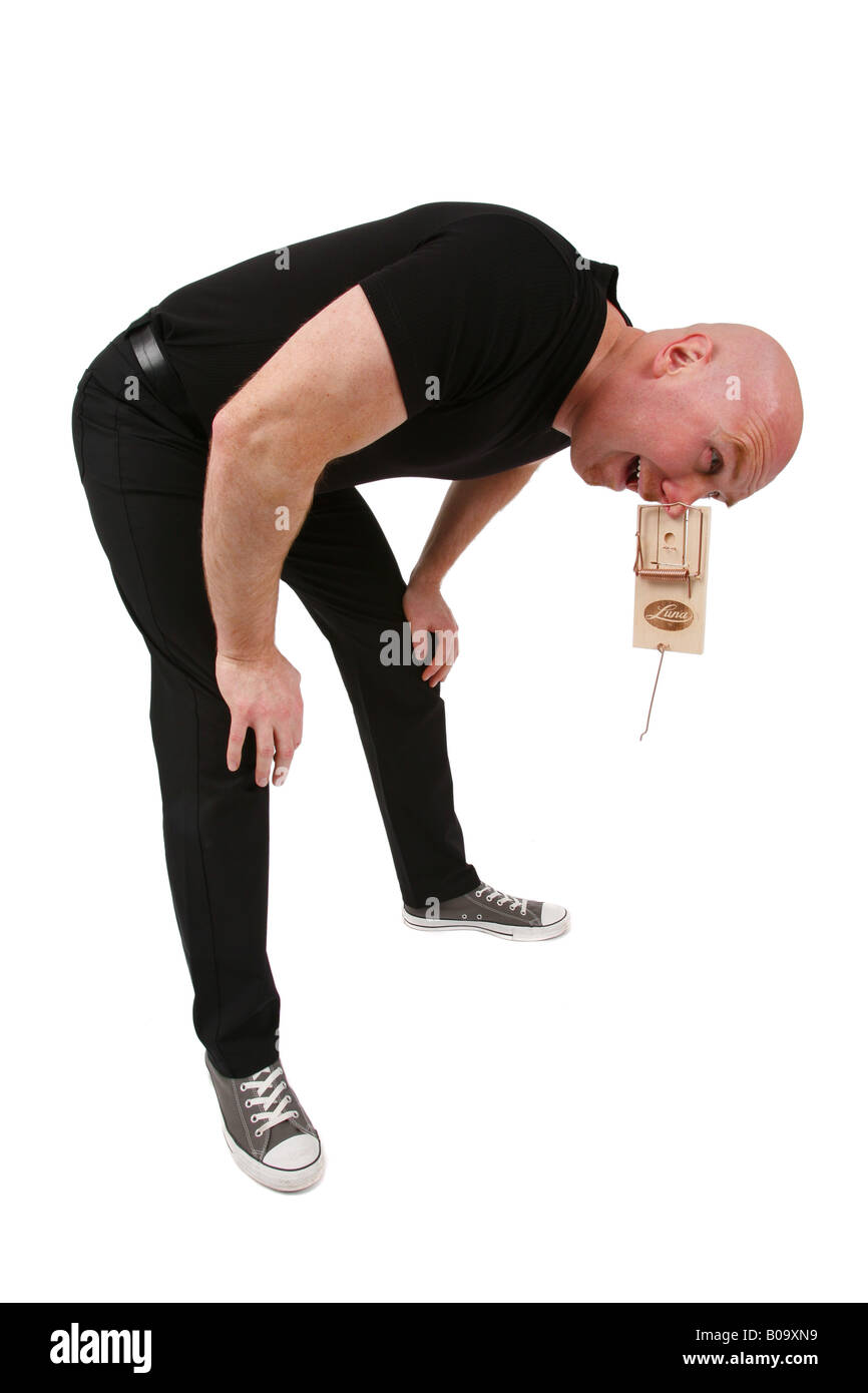 bald headed man with nose in mouse trap - Stock Image
