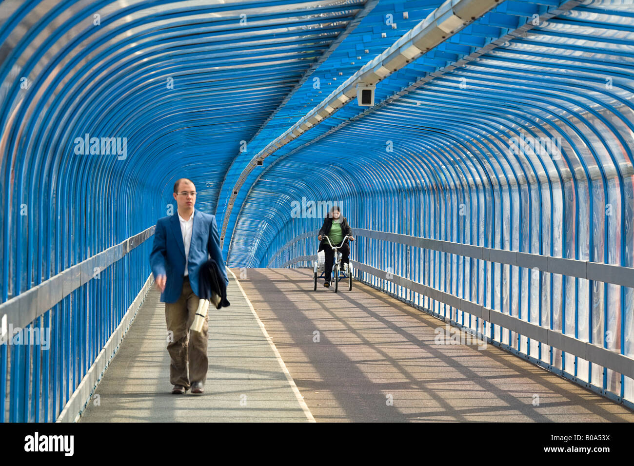 Pedestrian and cyclist on a three wheeled cycle crossing the Carter Bridge, Cambridge - Stock Image