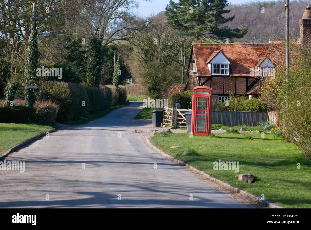 A tranquil English village scene with a traditional red telephone box standing on a country lane in the village - Stock Image