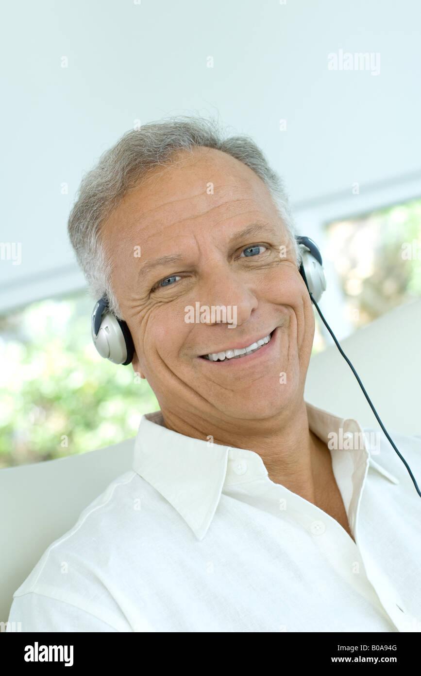 Mature man listening to headphones, smiling at camera, close-up - Stock Image
