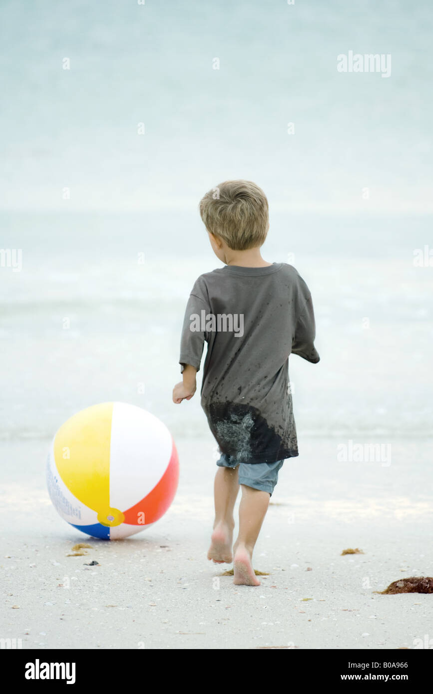 Little boy chasing beach ball at the beach, rear view - Stock Image