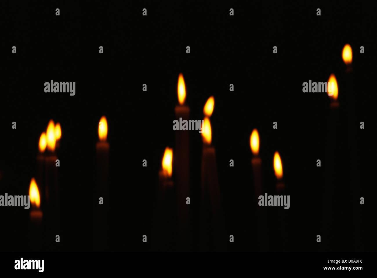 Several candles burning in the dark, full frame - Stock Image