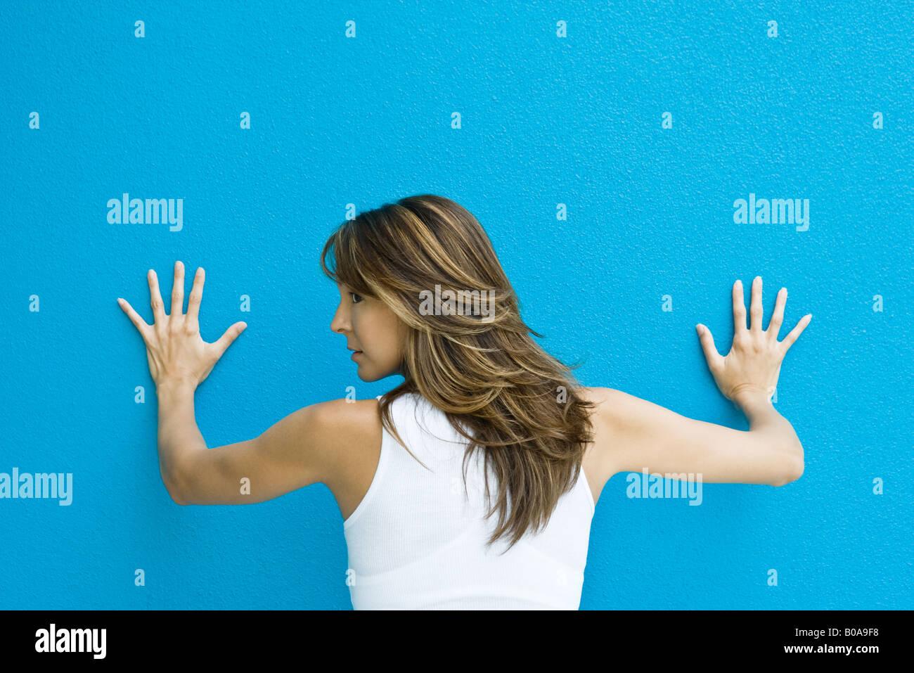 Woman standing with hands against blue wall, looking over shoulder, rear view - Stock Image
