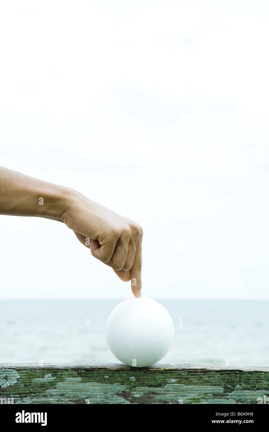 Man touching ball with index finger, cropped view of hand - Stock Image