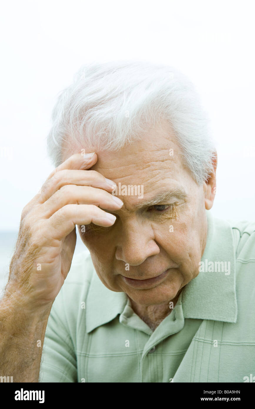 Senior man holding head, looking down, close-up - Stock Image