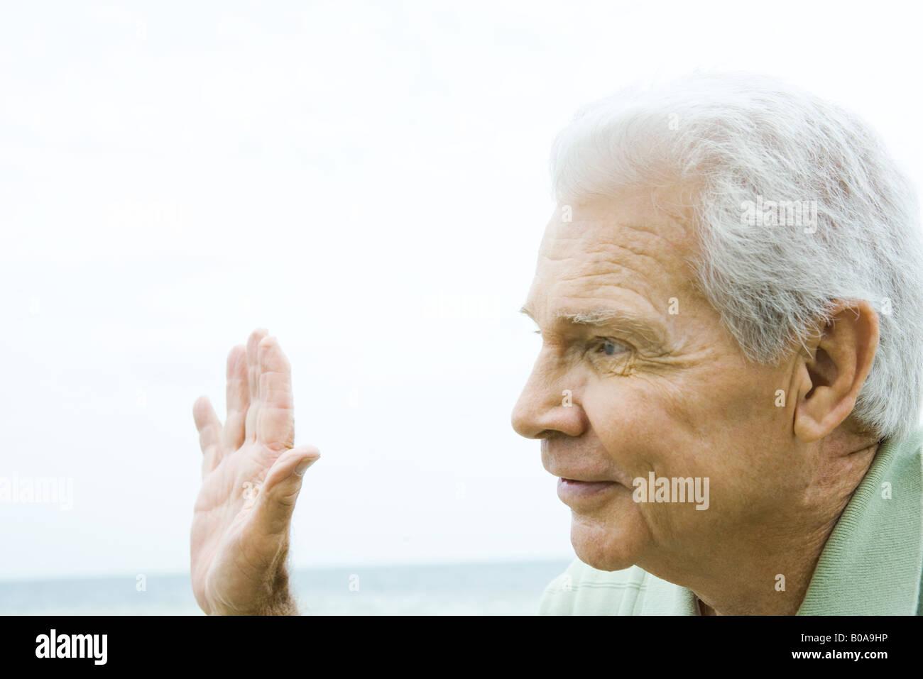 Senior man waving hand, smiling, side view - Stock Image