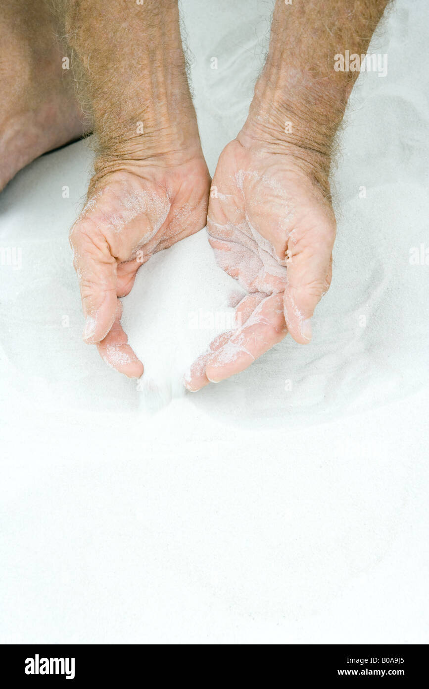 Man scooping sand in both hands, cropped view of hands - Stock Image