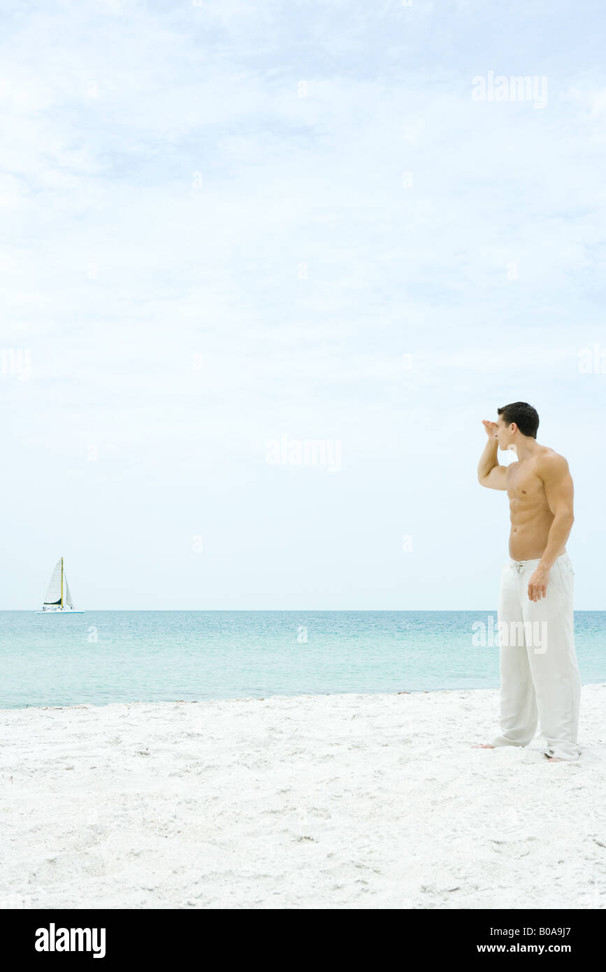 Man standing at the beach, looking at sailboat in the distance, side view - Stock Image