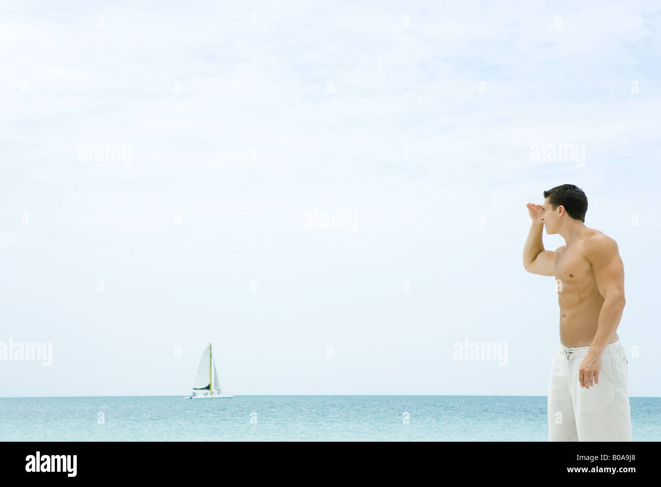 Man standing at the beach, looking at view, sailboat in the distance - Stock Image