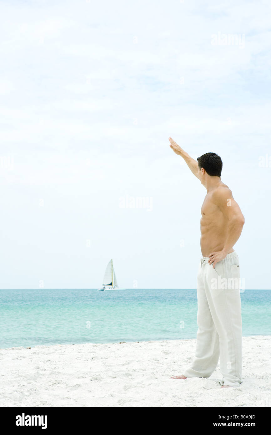 Man standing at the beach with arm raised, waving at sailboat in the distance, side view - Stock Image