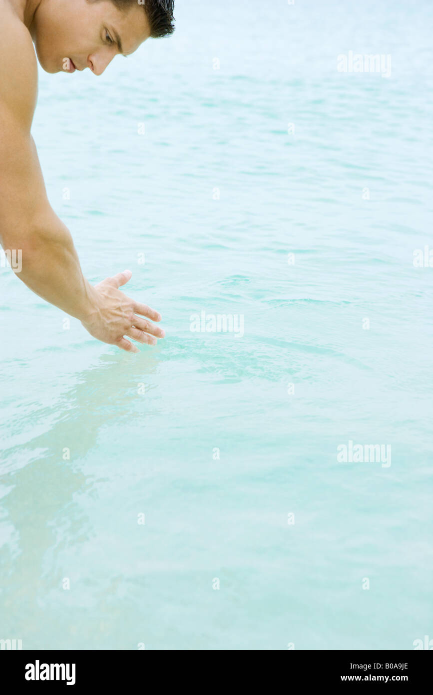 Man bending over, touching water, cropped view - Stock Image