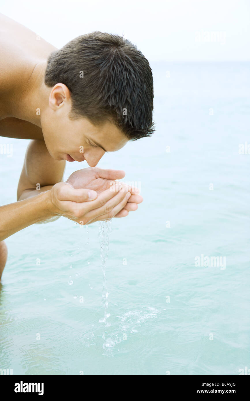 Man bending over, drinking water from hands, close-up - Stock Image