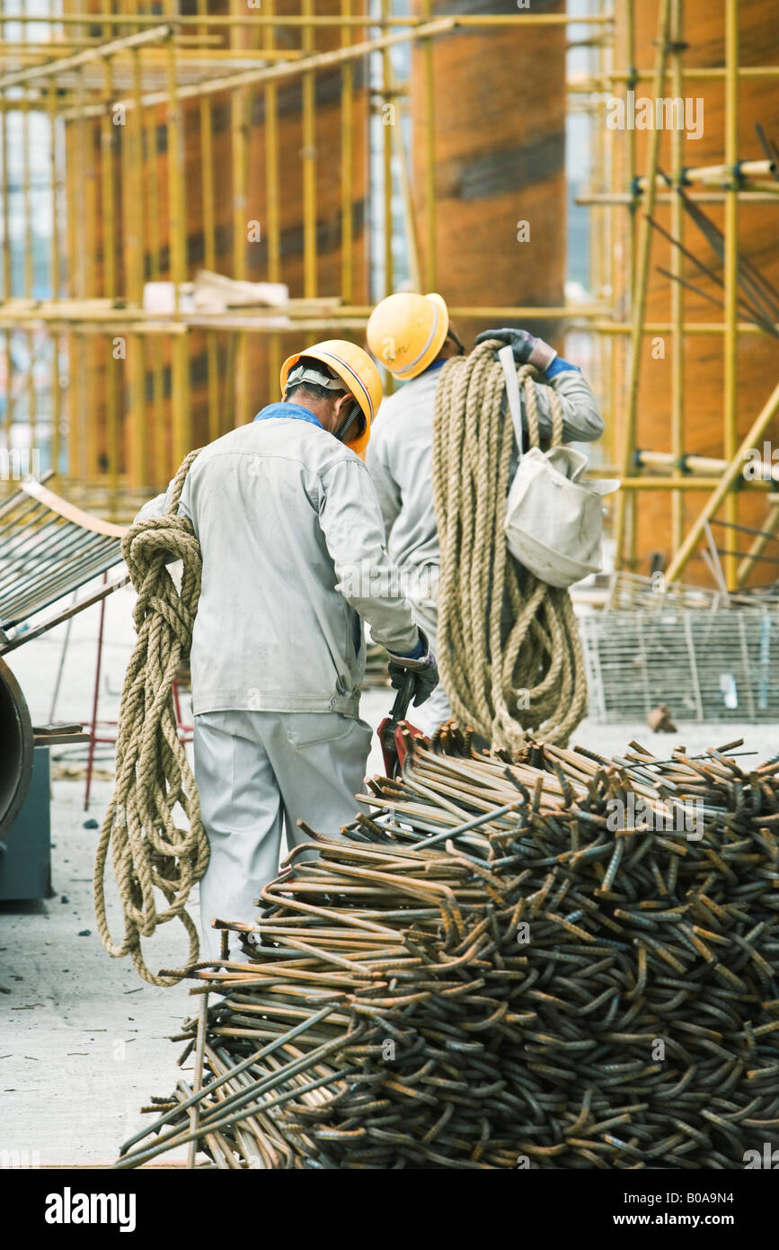 Workers at construction site carrying rope, metal rods stacked in foreground - Stock Image