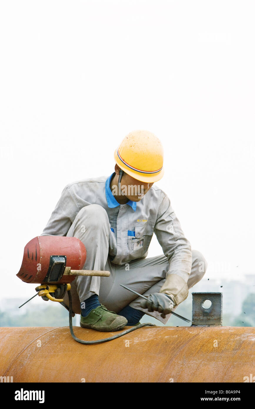 Worker crouching on metal pipe, holding welding mask, looking down Stock Photo