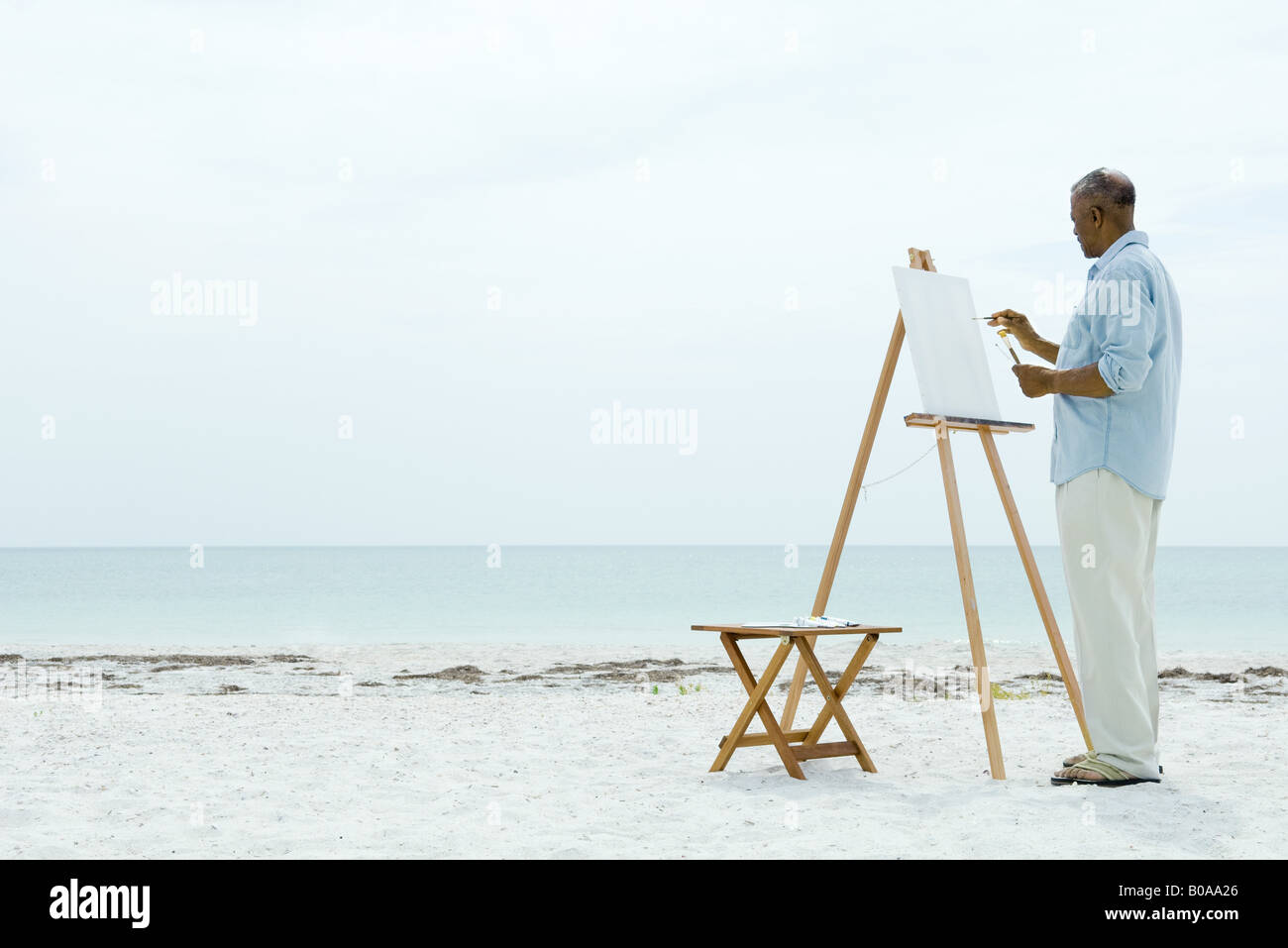 Senior man painting on canvas at the beach, side view - Stock Image