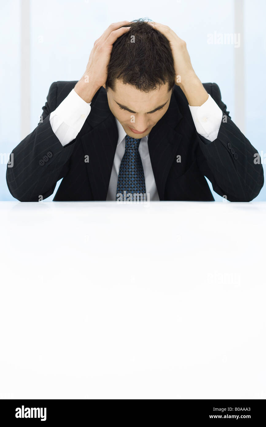 Businessman sitting, holding head, looking down - Stock Image