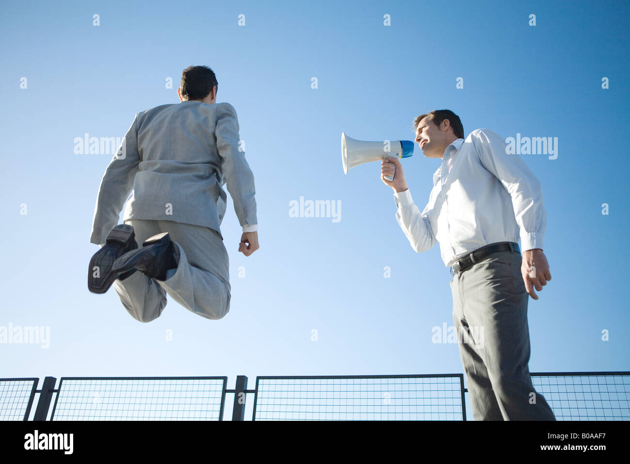 Businessman standing beside colleague, shouting into megaphone, colleague jumping in air, low angle view - Stock Image