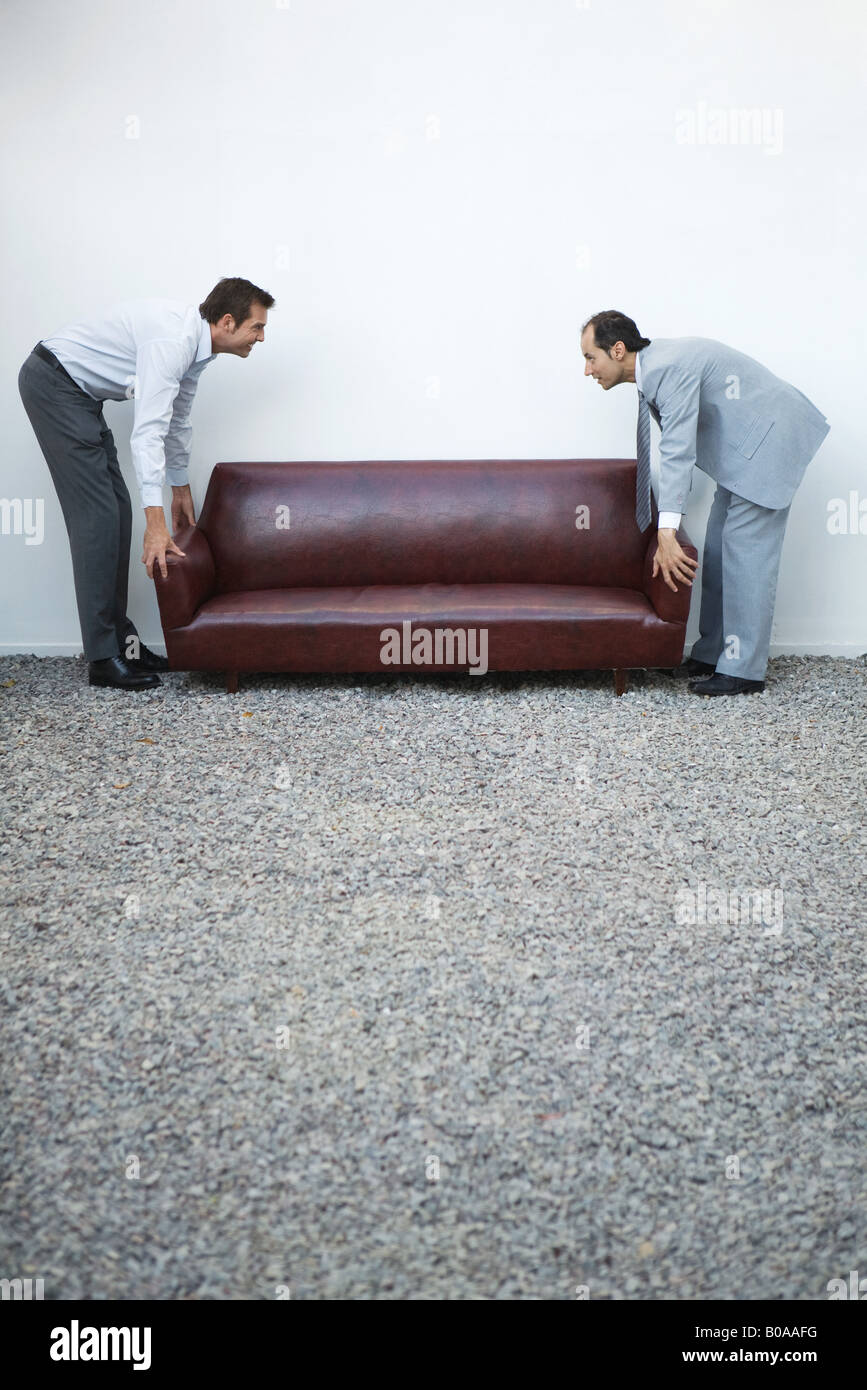 Two businessmen standing picking up sofa, looking at each other, side view - Stock Image