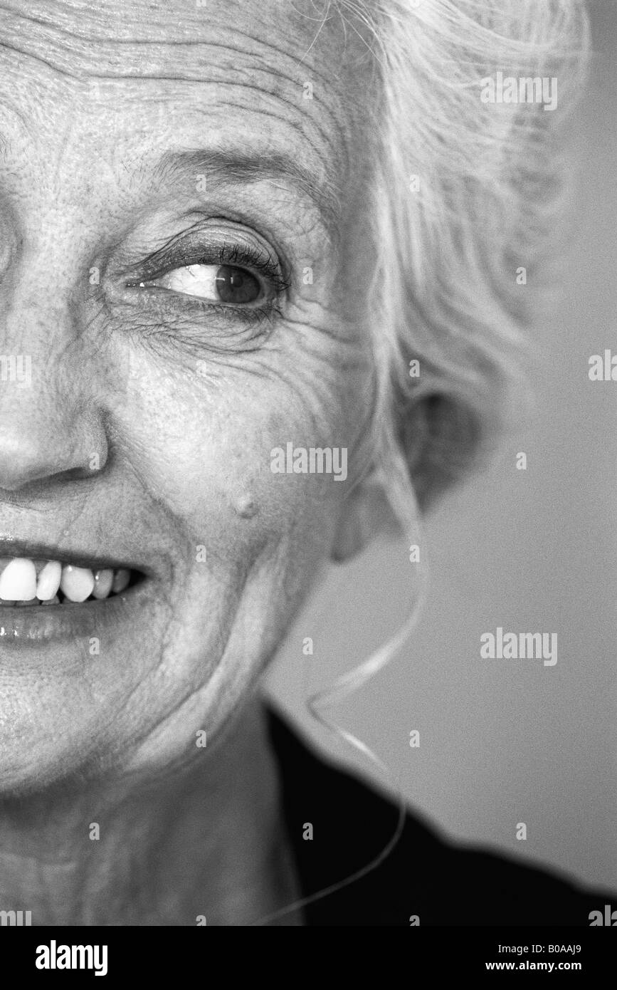 Senior woman looking away and smiling, portrait, cropped - Stock Image