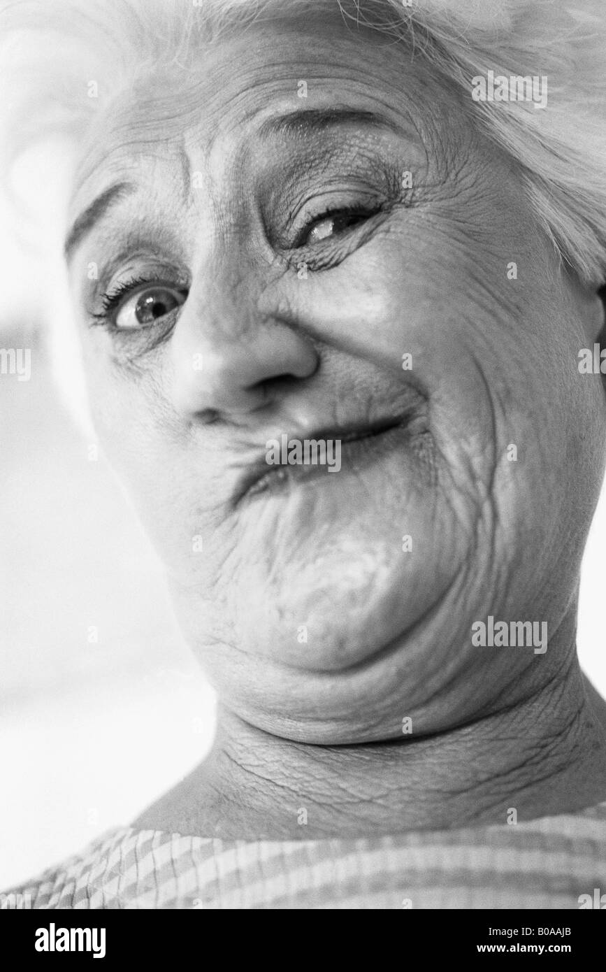 Senior woman making face at camera, portrait - Stock Image