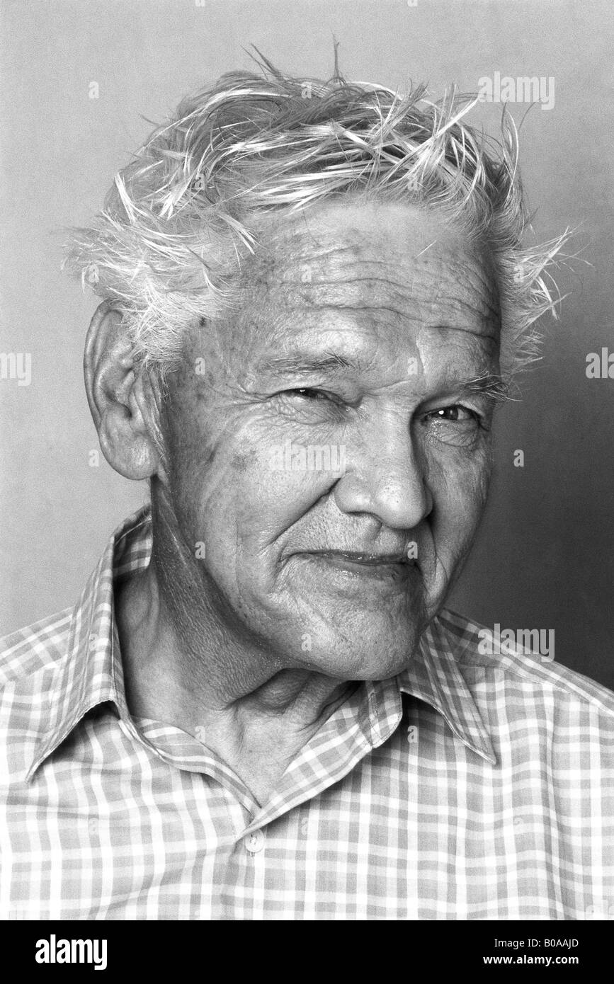 Senior man smiling at camera, portrait - Stock Image