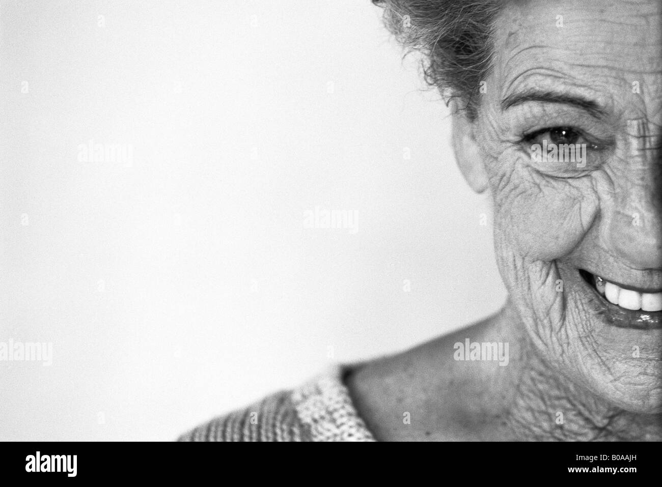 Senior woman smiling at camera, portrait, cropped - Stock Image