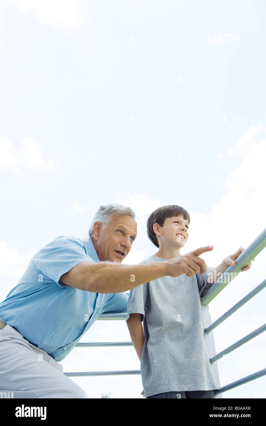Man standing with arm around grandson's shoulder, pointing, both looking away, low angle view - Stock Image