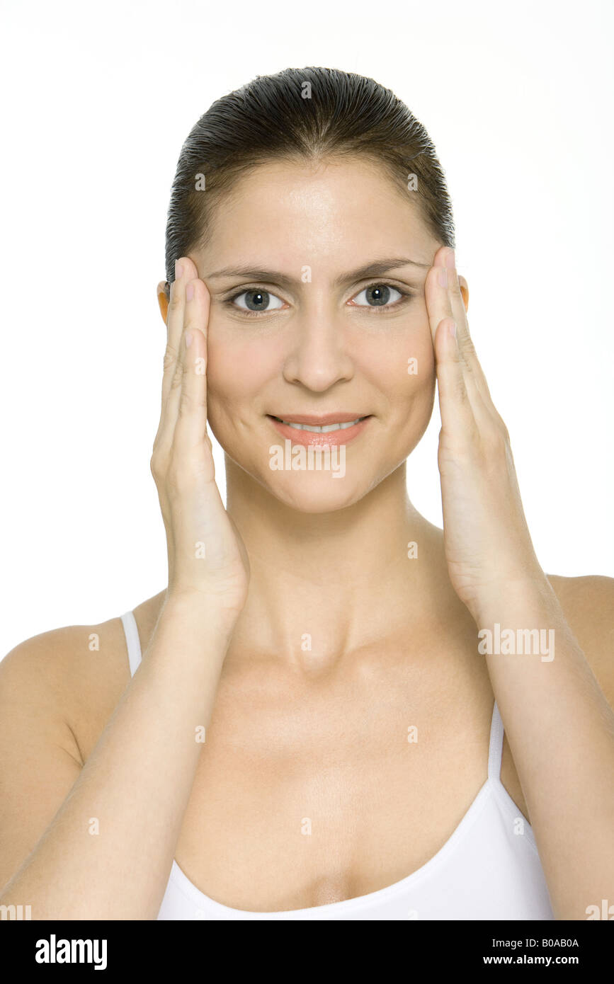 Woman holding face in hands, smiling at camera, portrait - Stock Image