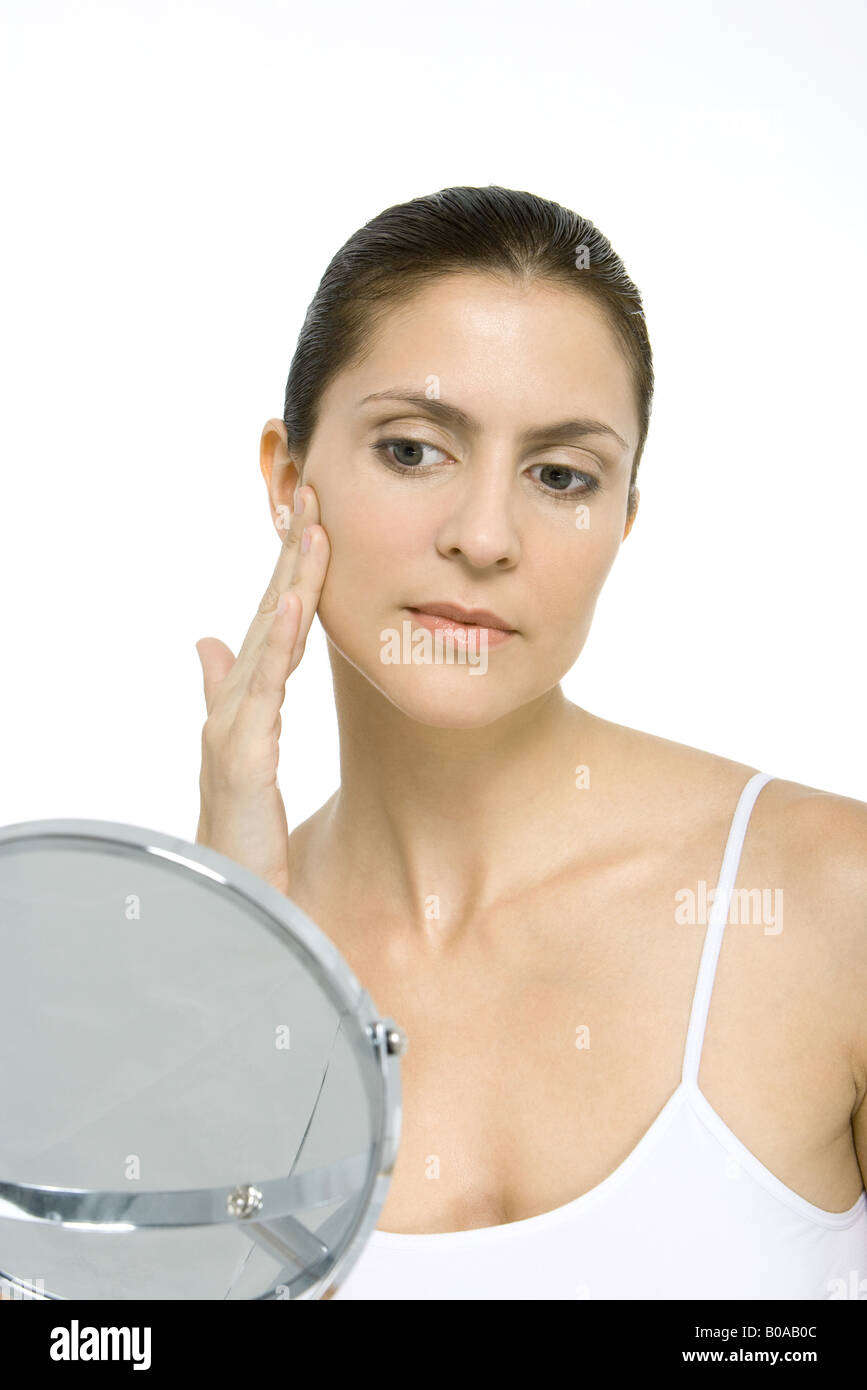 Woman looking at herself in mirror, touching cheek - Stock Image