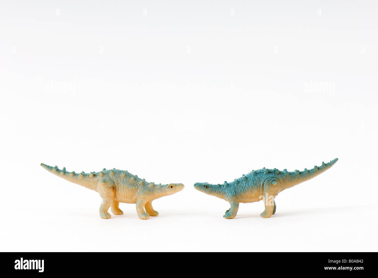 Toy dinosaurs facing each other - Stock Image