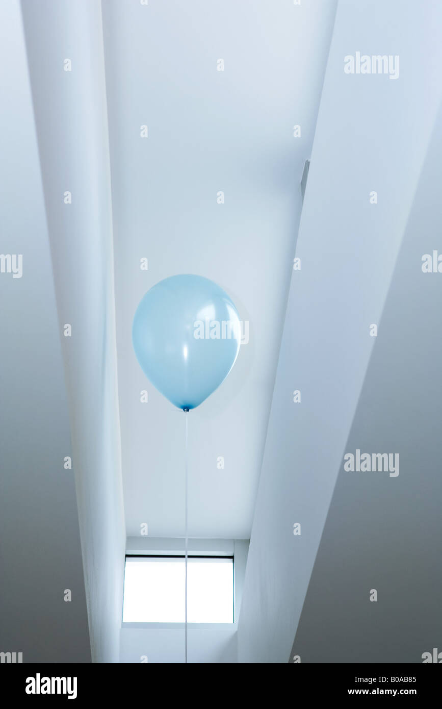 Balloon floating near against ceiling, low angle view - Stock Image