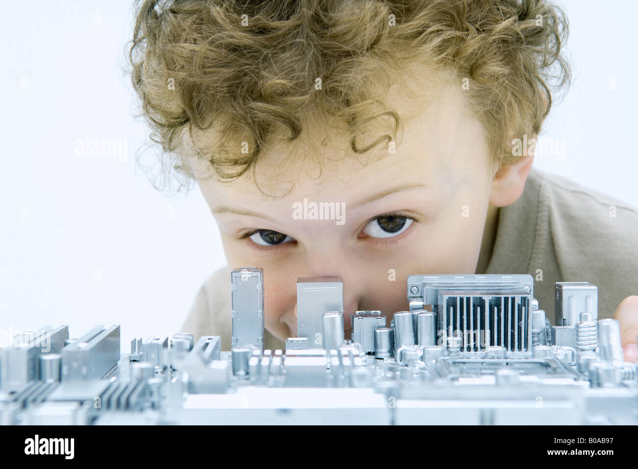 Little boy looking over circuit board at camera, close-up - Stock Image