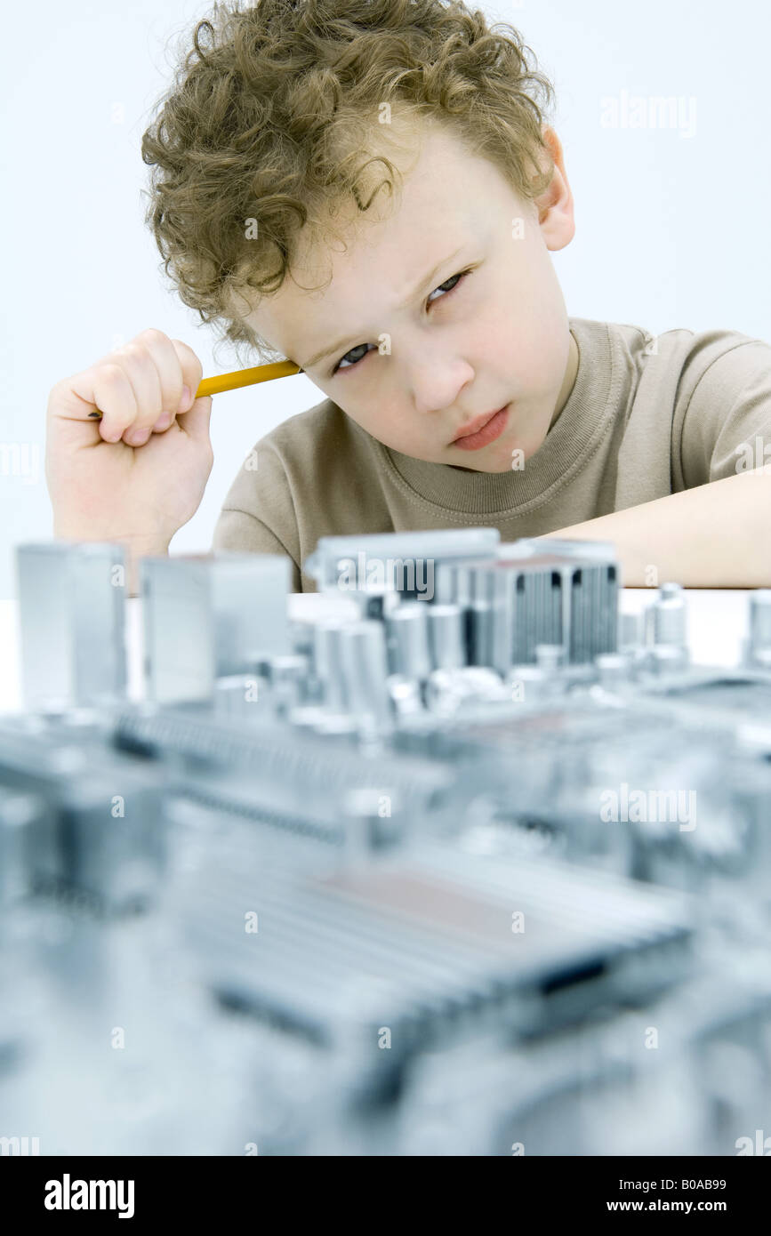 Little boy with circuit board, holding pencil, looking at camera - Stock Image