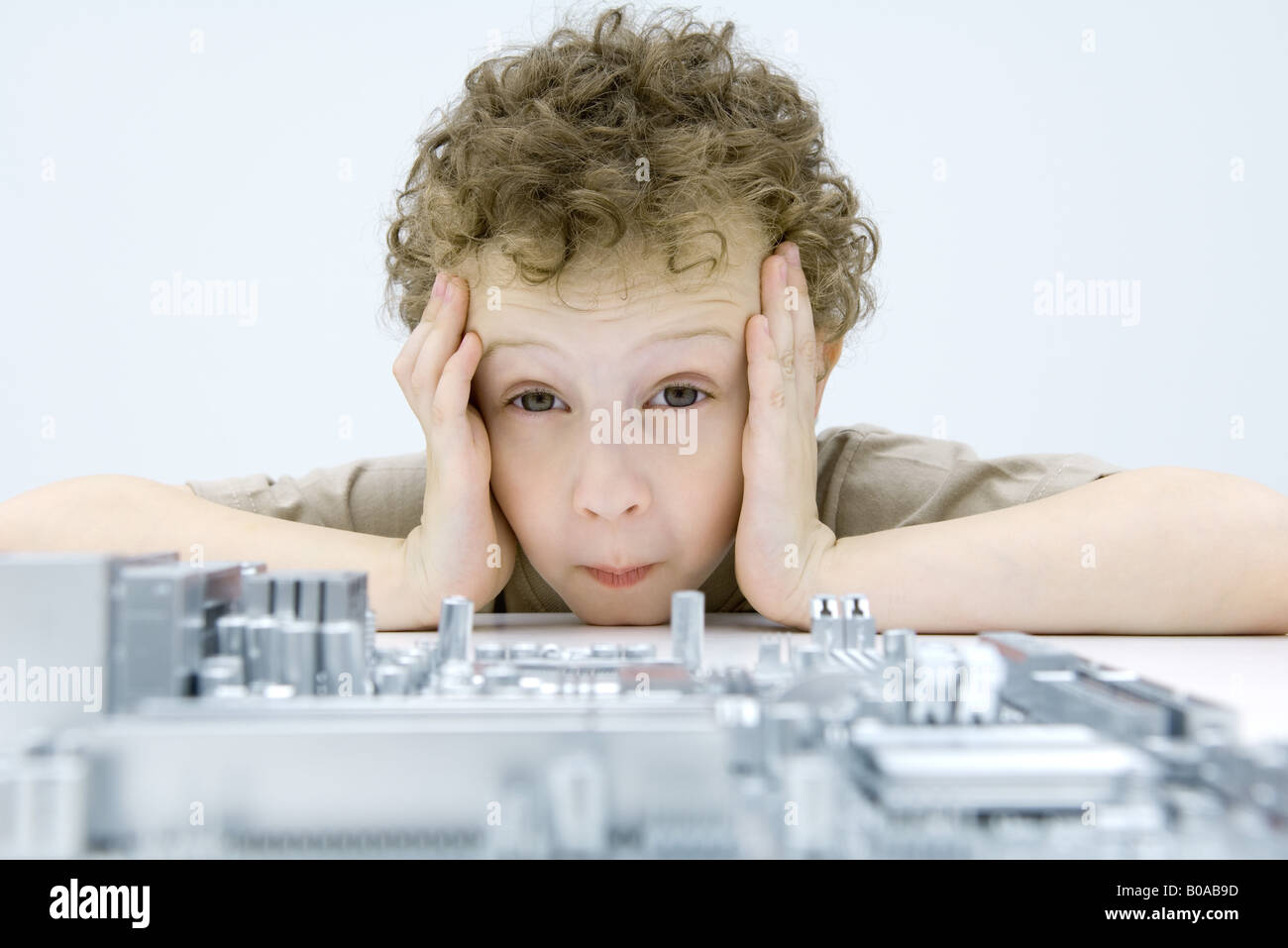Little boy looking at circuit board, holding head, raising eyebrows - Stock Image