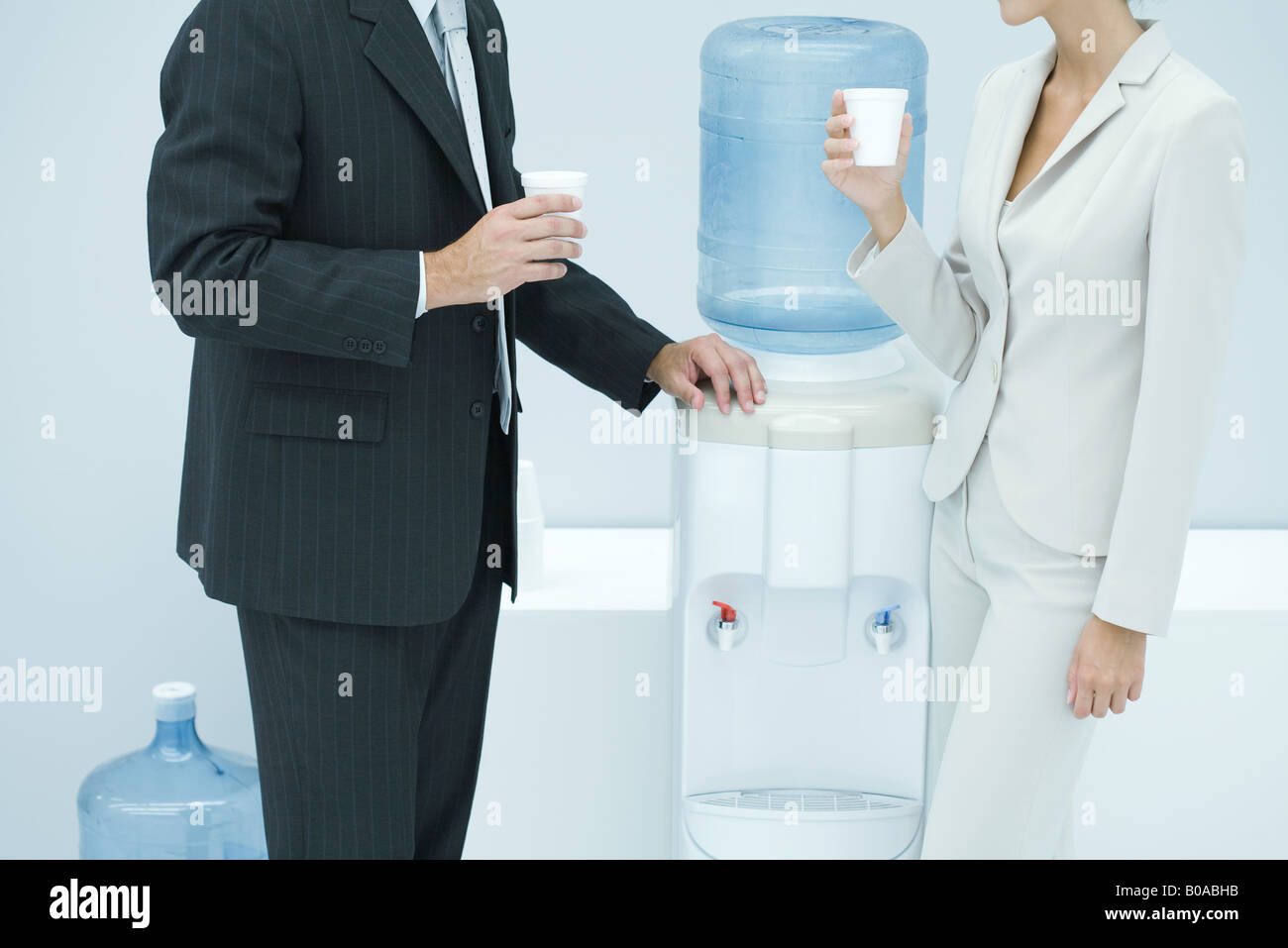Two business colleagues standing by water cooler, cropped - Stock Image