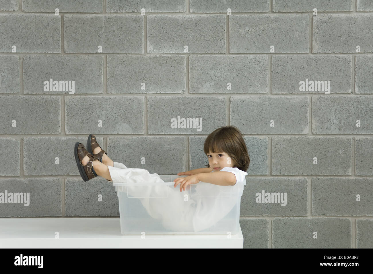 Little boy sitting inside plastic storage container, side view - Stock Image