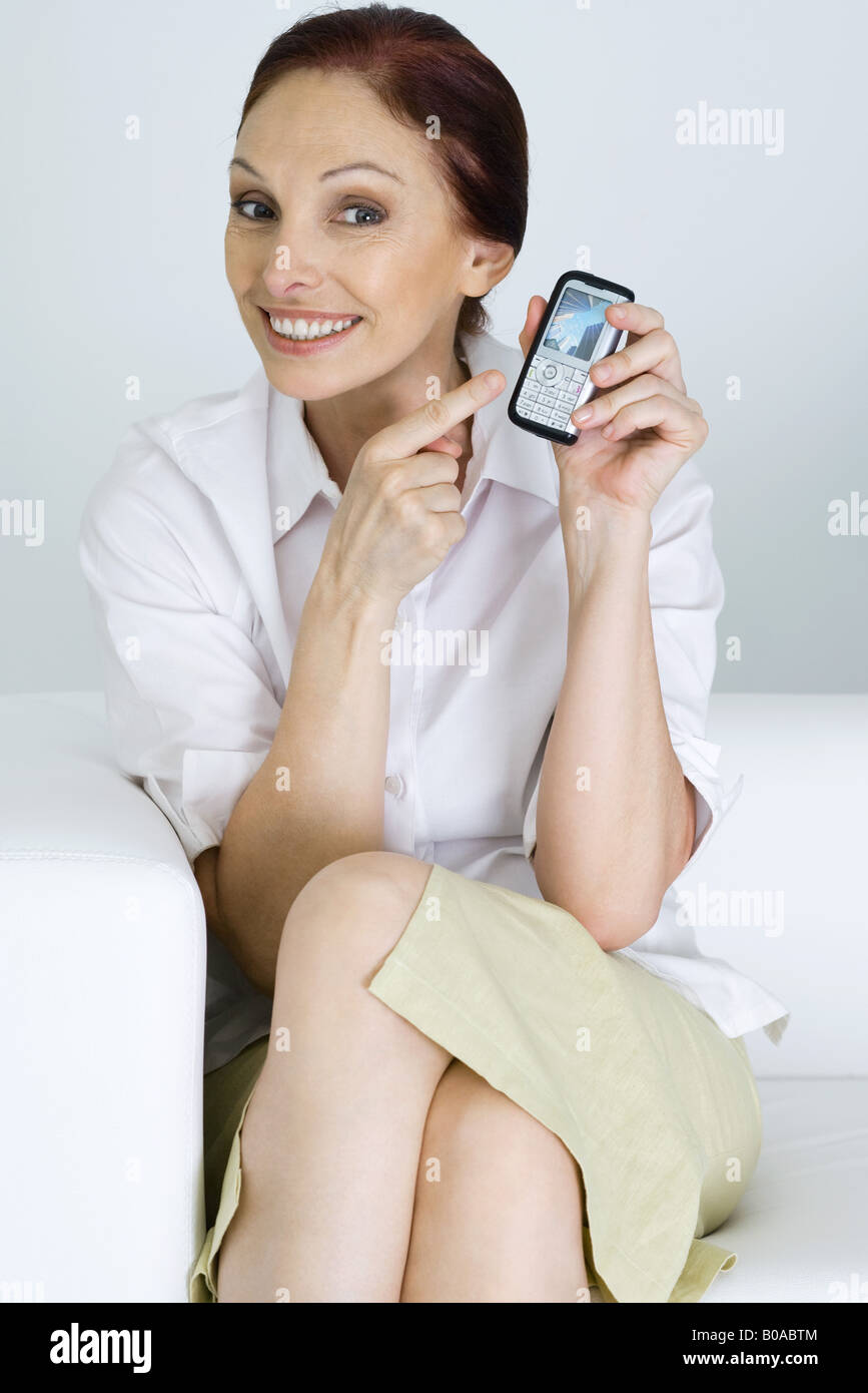 Woman pointing at cell phone in hand, smiling at camera - Stock Image