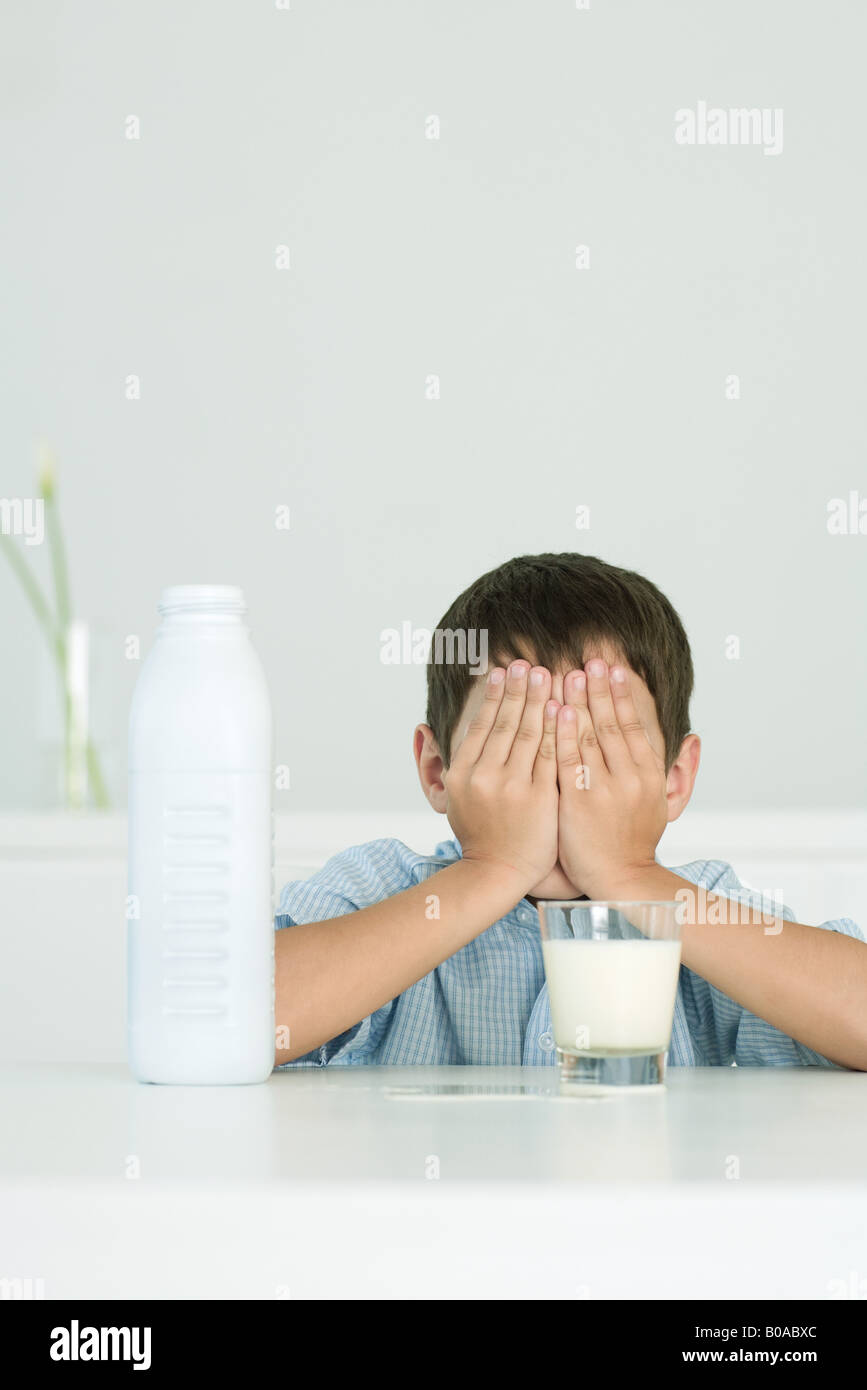 Little boy with glass of milk, covering eyes with hands - Stock Image