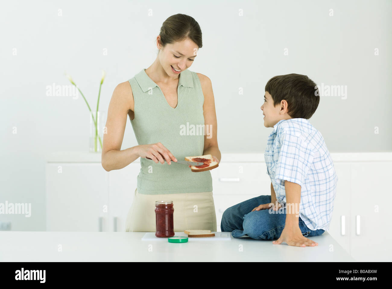 Mother spreading jam on bread, chatting with young son - Stock Image