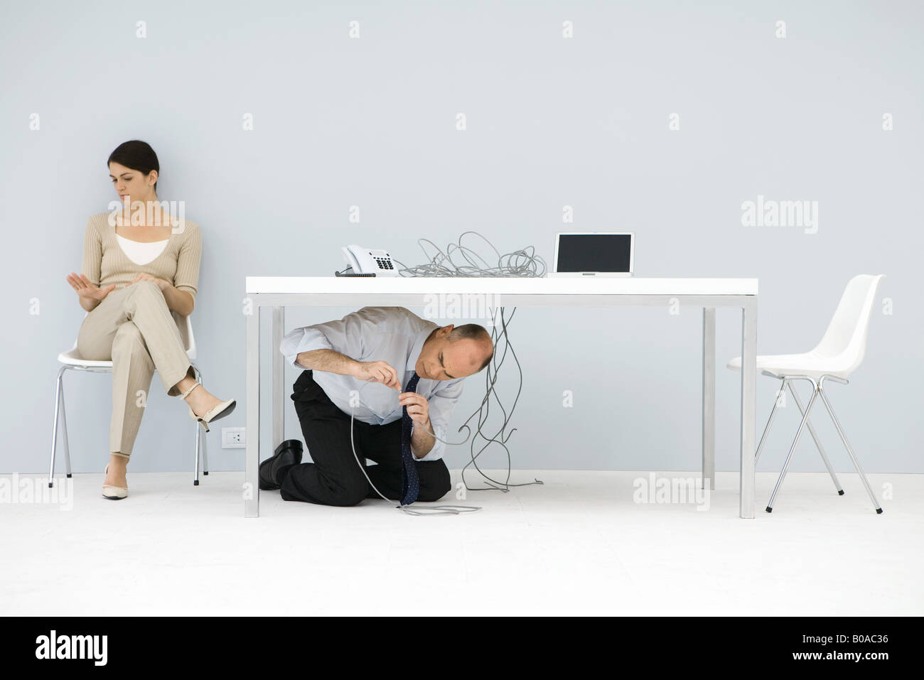 Man kneeling under desk, connecting tangled wires, woman sitting in chair, looking at hand - Stock Image